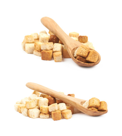Pile of garlic white bread croutons with a wooden spoon over it, composition isolated on the white background set of two different foreshortenings