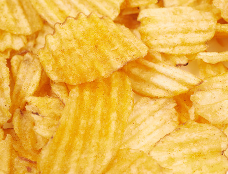 grasas saturadas: Surface covered with multiple seasoned potato chips crisps as a background composition