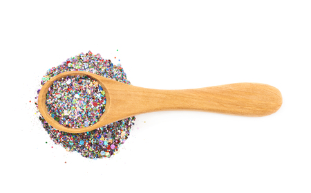 Wooden spoon full of sequins Stock Photo