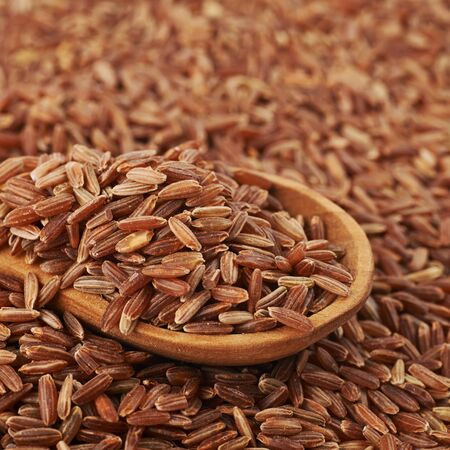 Surface coated with the brown rice grains and wooden serving spoon over it, as a food and cooking backdrop composition with a shallow depth of field Stock Photo