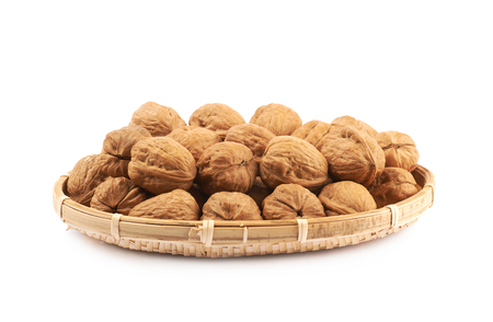 Wicker basket full of walnuts isolated over the white background