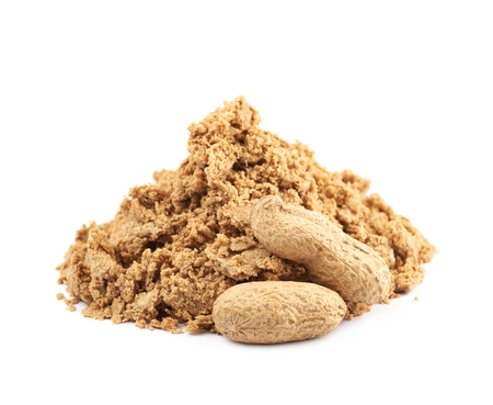 Pile of crushed and crumbled turkish halva confection next to a couple of peanuts, composition isolated over the white background