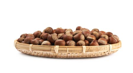 Wicker basket of hazelnuts isolated over the white background