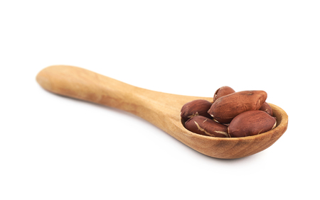 nutshells: Spoon full of peanuts isolated