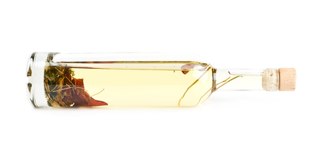 Glass bottle of olive oil fermented with the herbs and peppers, lying on its side, composition isolated over the white background