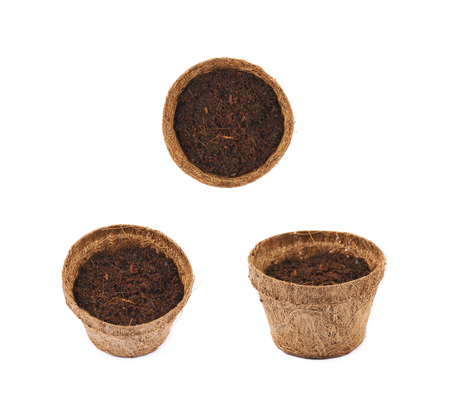 Degradable coconut pot filled with the earth soil, composition isolated over the white background, set of three different foreshortenings Stock Photo