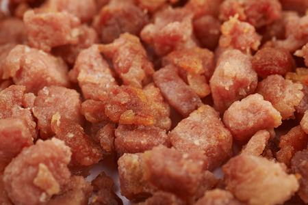 pancetta cubetti: Surface covered with the fried cube bacon bits as a food backdrop composition with a shallow depth of field