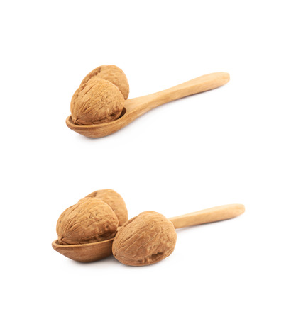 Walnut in a wooden spoon isolated over the white background, set of two different foreshortenings Stock Photo