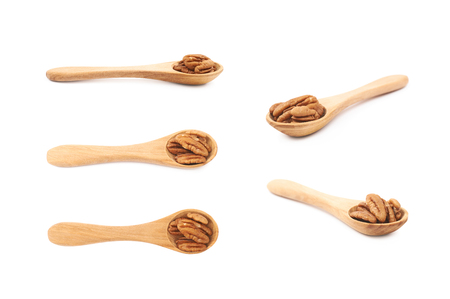 Wooden spoon full of pecan nuts isolated over the white background, set of five different foreshortenings