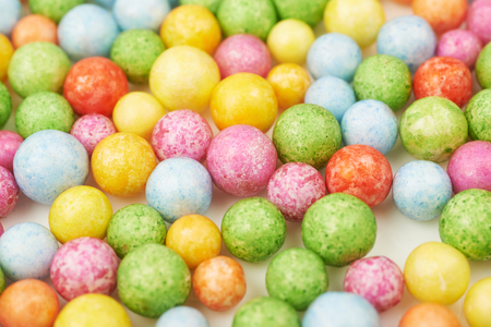 Surface coated with colorful balls or sphere shaped breakfast cereals as an abstract backdrop composition Stock Photo