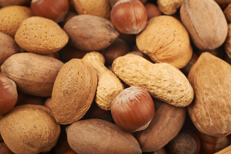 Close-up crop of a surface coated with the different kinds of nuts as a food backdrop composition