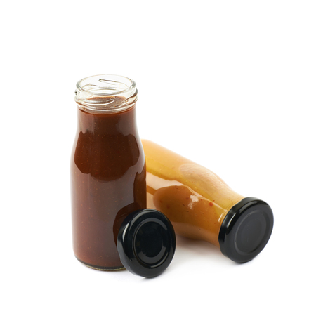 Composition of two sauce condiments in glass jar bottles next to each other, isolated over the white background