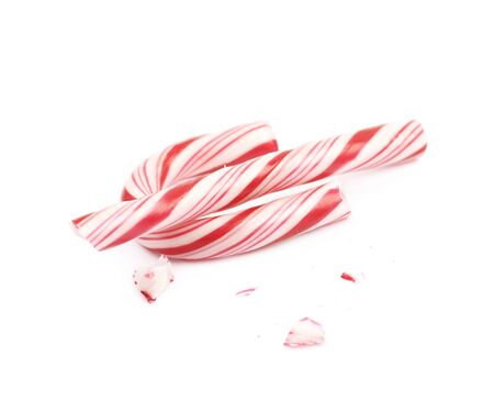 Christmas sweet candy cane, broken into multiple pieces, composition isolated over the white background Stock Photo