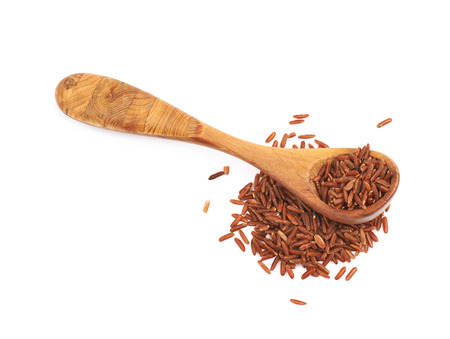 Pile of red rice with the wooden spoon over it, composition isolated over the white background Stock Photo