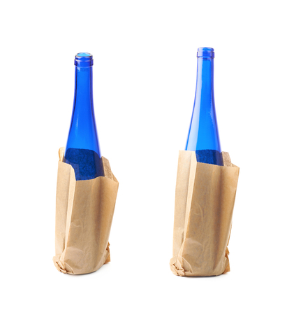 Colored glass bottle hidden in a paper bag, composition isolated over the white background , set of several different foreshortenings