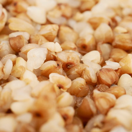 Surface coated with the cooked buckwheat seeds as a backdrop composition texture with the shallow depth of field