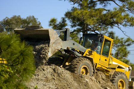 A front-end loader moving a pile of dirt photo