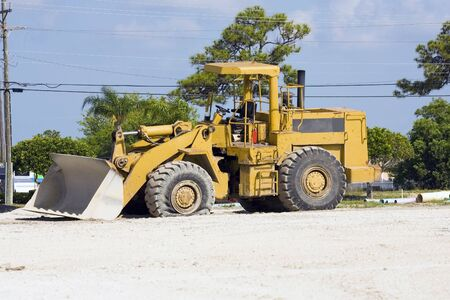 frontend: A front-end loader with a flat tire Stock Photo