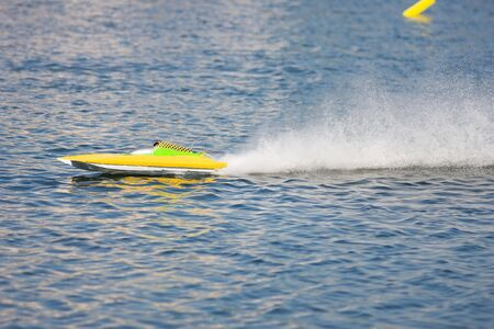 rc: RC model boat doing practice laps around yellow pilings