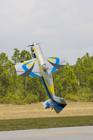 An RC stunt model airplane doing a tail stand under power