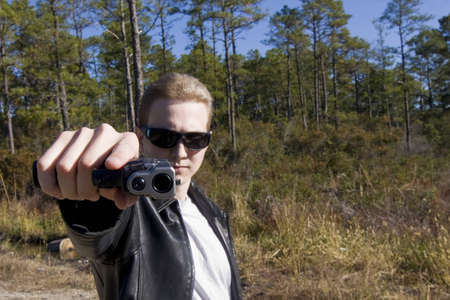 A punk in t-shirt and leather jacket points a pistol at viewer. photo