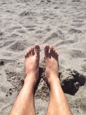 Shot of legs in the sand.