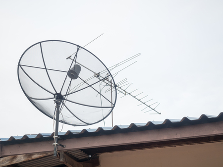 satelite: Black satellite dish mounted on a wall outside the house. A drop of