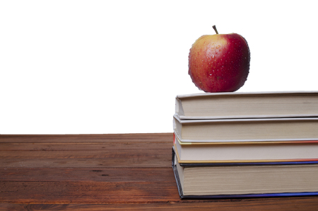 apple on books on a wooden board