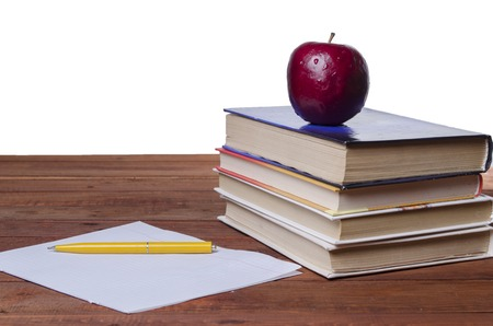 investigates: apple on books on a wooden board