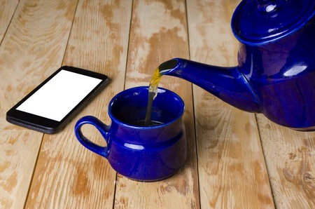 stimulated: blue ware for tea and phone on a wooden board