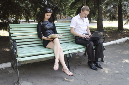 fellow: fellow with a girl on a bench in a sunny day
