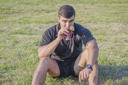 satisfies: the athlete satisfies thirst on the street Stock Photo