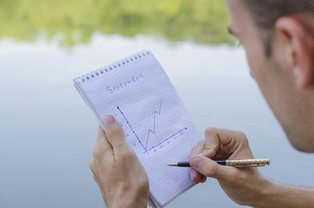 cuadro sinoptico: el chico joven escribe en un cuaderno al aire libre Foto de archivo