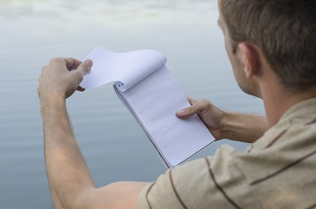 the young guy writes in a notebook in the open air Stock Photo