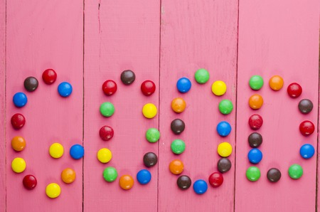 well laid: bright candies on a wooden pink table
