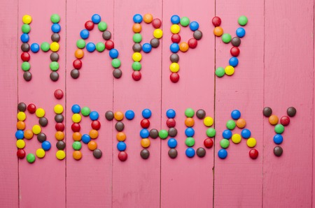 chocolate candy: beautiful inscription from candies on a wooden pink background Stock Photo