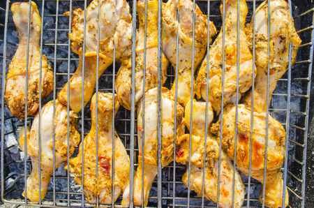 entertaining area: preparation of chicken meat on a fire in sunny day