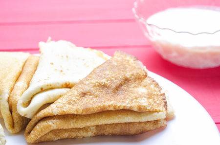 pancake week: fried pancakes in a white plate with sour cream Stock Photo