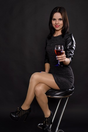 girl in a black dress drinking wine in the studio