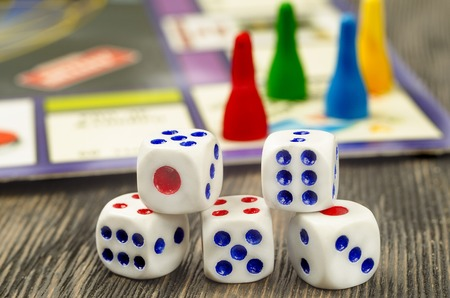 monopolio: White dices for board games on a black wooden table