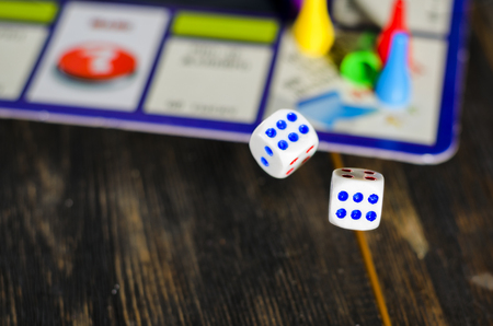 monopolio: Gambling board game with white cubes on a wooden table Foto de archivo