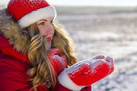 girl holds snow in red mittens in winter on the street