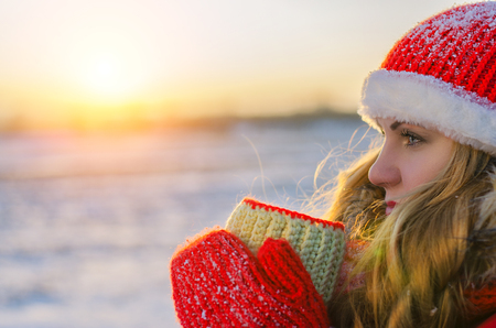 girl with a cup of hot drink in winter on a sunset background