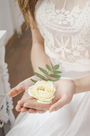 Mädchen , das eine Rose mit einem Goldring in ihrem Hochzeitskleid hält Standard-Bild - 91455275
