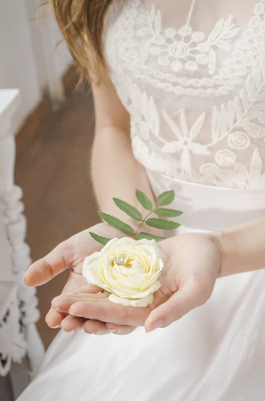 girl holding a rose with a gold ring in her wedding dress Foto de archivo
