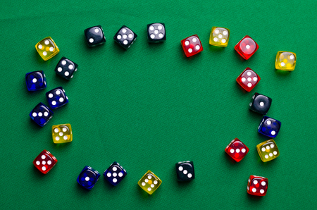 multi-colored dice for table games on a green table Stock Photo