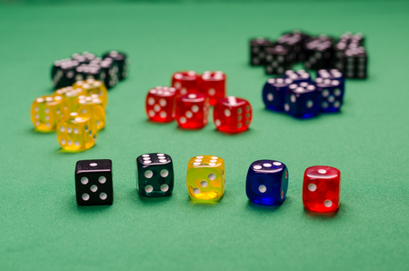 multi-colored cubes for the board game are on the green table Stock Photo