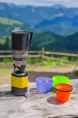 steel mug on a gas stove with plastic glasses in the mountains