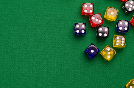 several multi-colored cubes lie on a green table