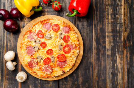 homemade pizza with tomatoes and mushrooms on a wooden table with vegetables